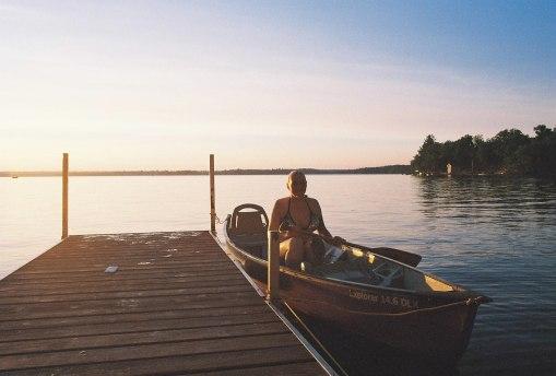 women in canoe on lake sunset