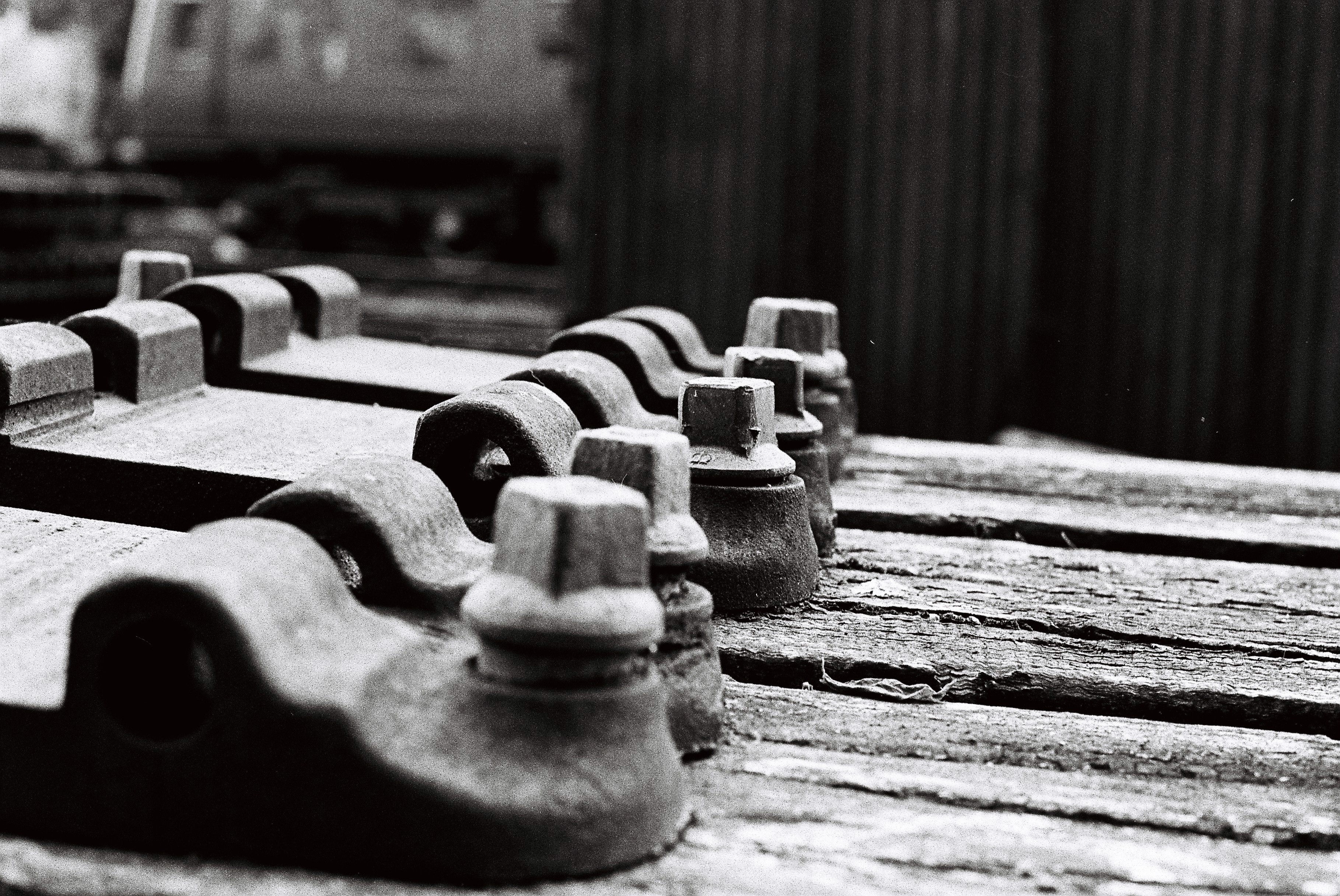 black and white film photography train bolts